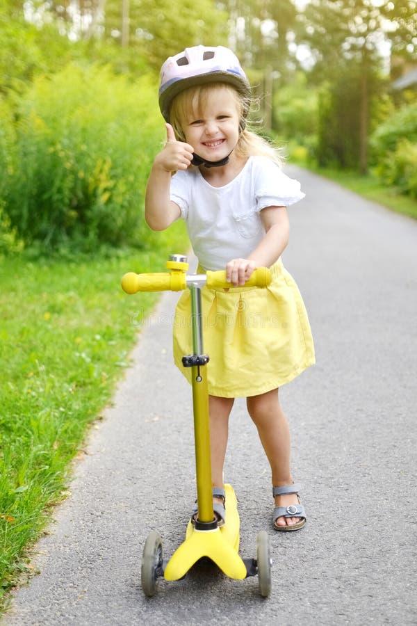 'trotinette' branco exterior, capacete do pontapé da equitação da camisa da saia feliz do amarelo da menina de segurança cor-de-r imagem de stock