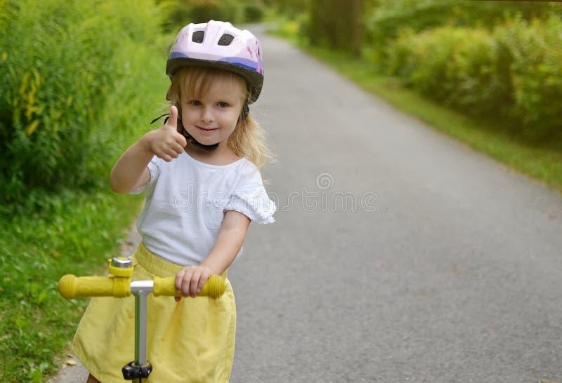 'trotinette' branco exterior, capacete do pontapé da equitação da camisa da saia feliz do amarelo da menina de segurança cor-de-r fotografia de stock royalty free