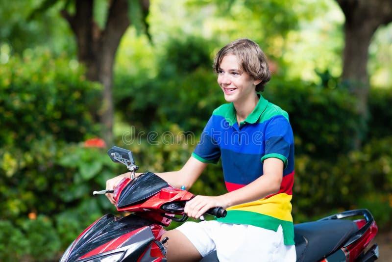 'trotinette' da equitação do adolescente Menino na motocicleta fotografia de stock