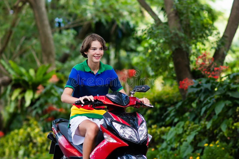'trotinette' da equitação do adolescente Menino na motocicleta imagens de stock royalty free