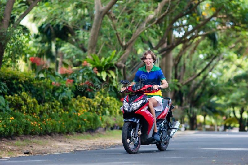 'trotinette' da equitação do adolescente Menino na motocicleta foto de stock