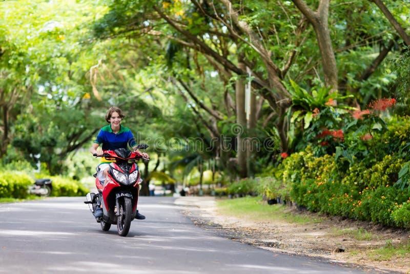 'trotinette' da equitação do adolescente Menino na motocicleta imagem de stock royalty free