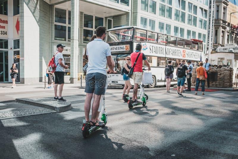 'trotinette', escooter ou e-'trotinette' elétrico da equitação do grupo do turista na rua em Berlim fotos de stock