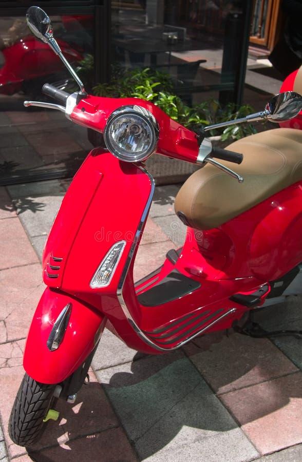 'trotinette' italiano retro vermelho do estilo estacionado na rua fotografia de stock royalty free