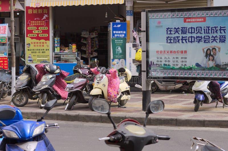 'trotinette's chineses na frente de um mercado imagem de stock royalty free