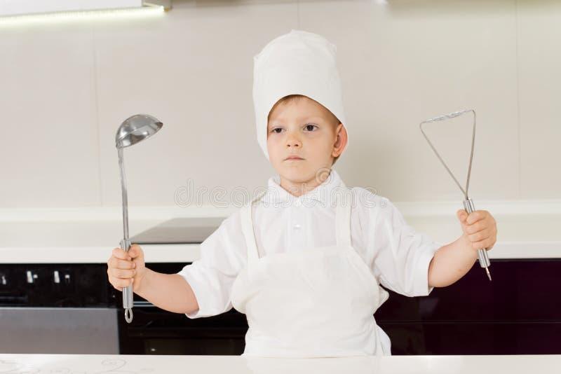 Trots weinig jongenschef-kok die zijn werktuigen steunen stock afbeeldingen