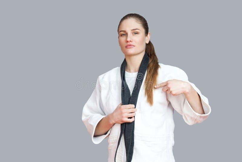 Trotse aantrekkelijke atletische vrouw in witte kimono status en wra stock foto