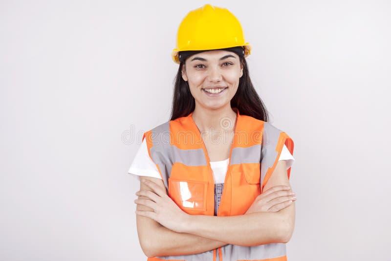 Trotse ernstige jonge vrouwenarchitect of ingenieur met wapens die als professioneel concept worden gekruist van de de bouwsuperv royalty-vrije stock foto's