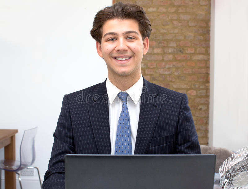 Trotse glimlachende jonge zakenman bij zijn bureau royalty-vrije stock foto's