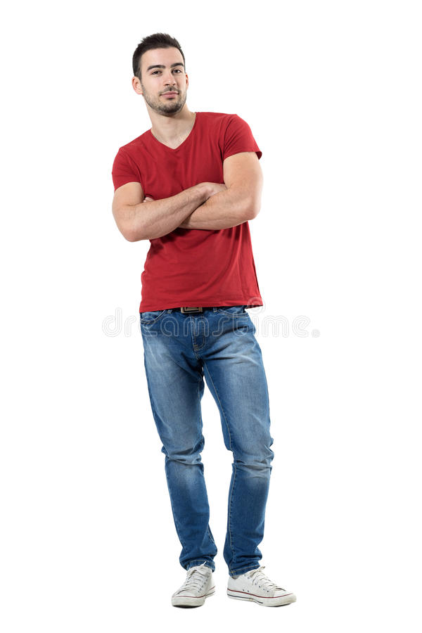 Trotse jonge toevallige in mens die in rode t-shirt met gekruiste handen camera bekijken royalty-vrije stock fotografie