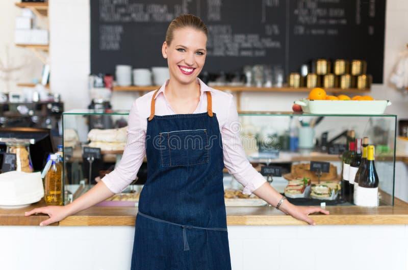 Trotse jonge vrouwelijke koffieeigenaar stock foto's