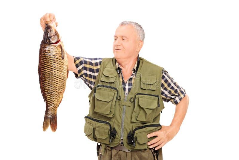 Trotse rijpe visser die een grote vis houden royalty-vrije stock fotografie