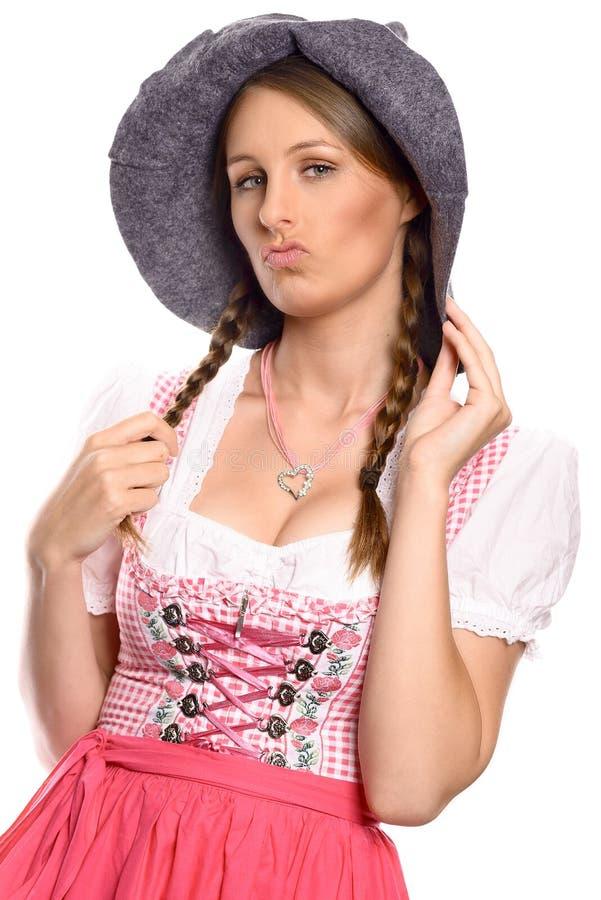 Trotse vrouw, die een rustieke hoed en een dirndl dragen stock afbeelding