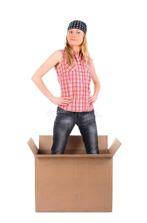 Trotse vrouw die zich in een kartondoos bevindt stock afbeeldingen