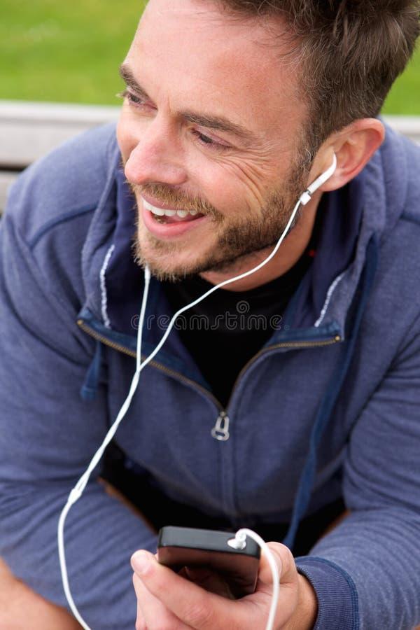 Trotteur heureux s'asseyant avec des écouteurs photographie stock libre de droits