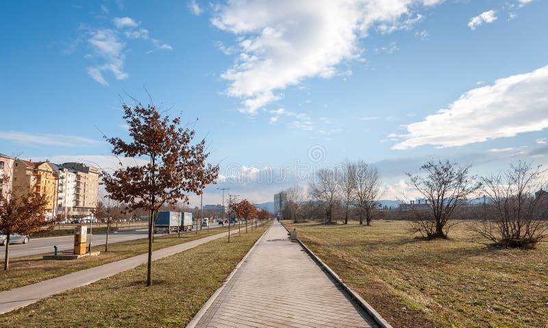Trottoar för den fot- gångbanan eller trottoarmed parkerar på den en vägen för sidan och för stads- trafik på annan i stadsgatan  arkivfoto