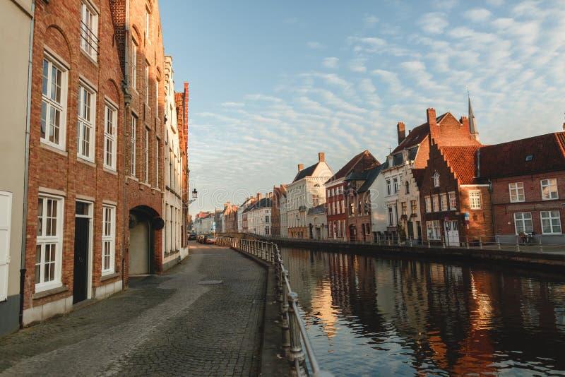 trottoar, härliga färgrika hus och kanal i brugge, Belgien royaltyfri bild