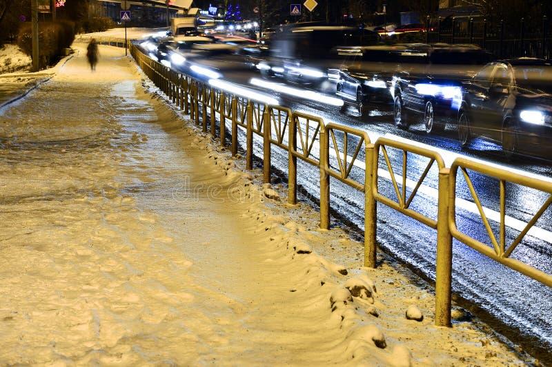 Trottoar i snö- och stadsvägarna med bilar i rörelse i aftonen suddigheta lampor arkivfoton