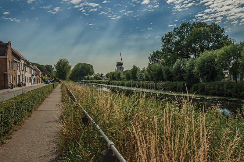Trottoar längs kanalen med hus, buskar och dunge, i den sena eftermiddagen och den blåa himlen, nära Damme royaltyfria bilder