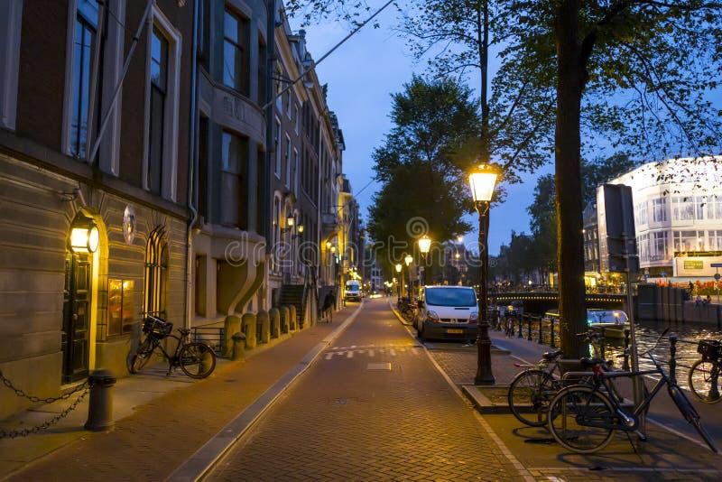 Trottoarerna på kanalerna av Amsterdam vid natt - AMSTERDAM - NEDERLÄNDERNA - JULI 20, 2017 royaltyfri bild