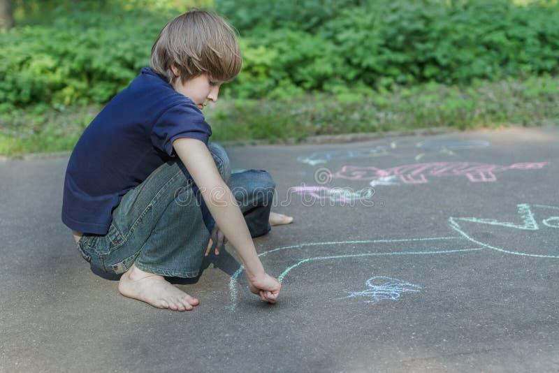 Trottoarkritateckningar av den barfota tonårs- pojken som bär den blå t-skjortan och jeans royaltyfria bilder