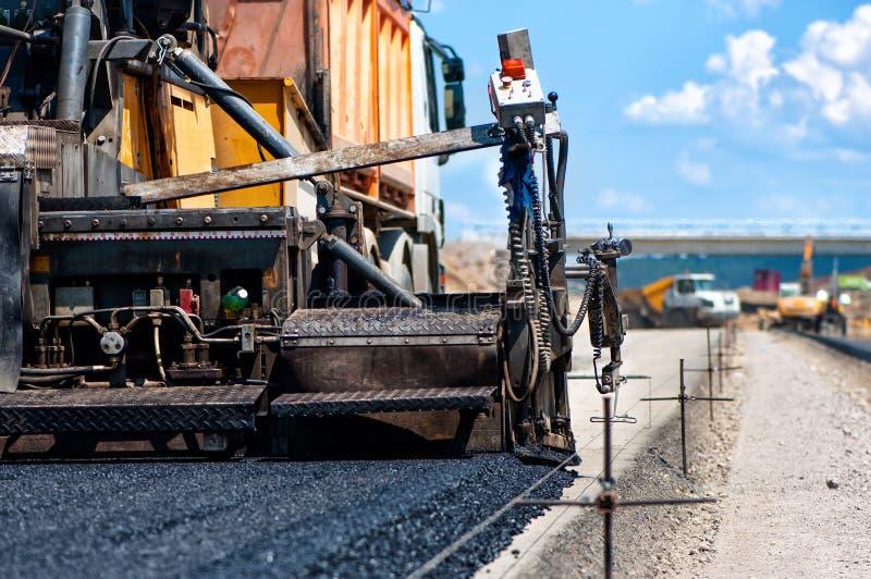 Trottoarmaskin som lägger ny asfalt eller bitumen royaltyfria bilder