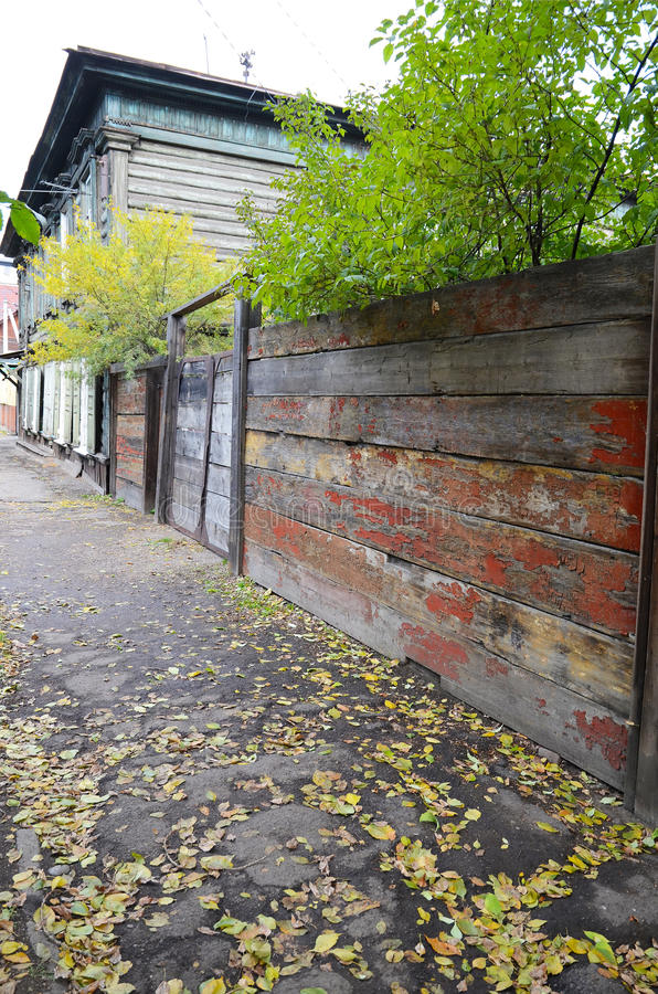 Trottoir avec les feuilles tombées de jaune et la vieille barrière minable Rue d'Irkoutsk photos stock