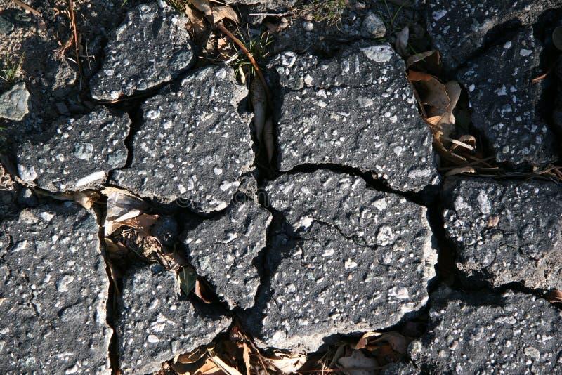 Trottoir cassé criqué d'asphalte image stock