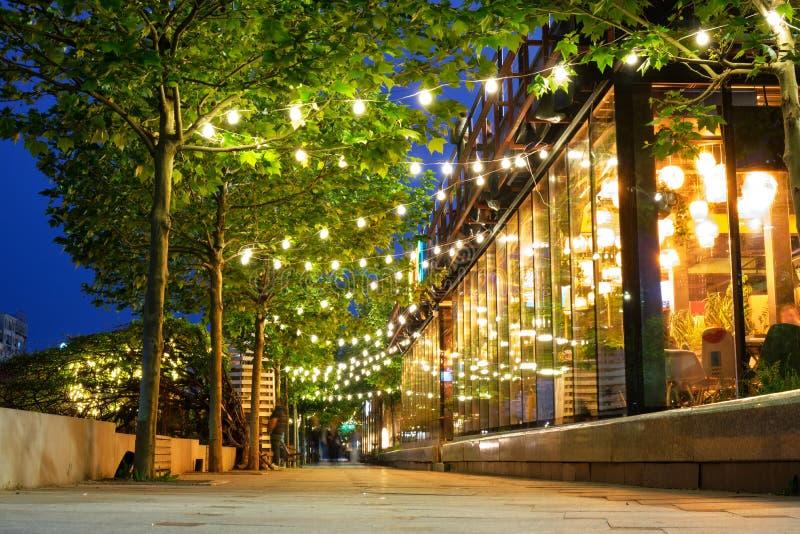 Trottoir décoré et lumineux avec une ligne des arbres, à l'heure bleue Lumières entrant des barres et des restaurants photo stock