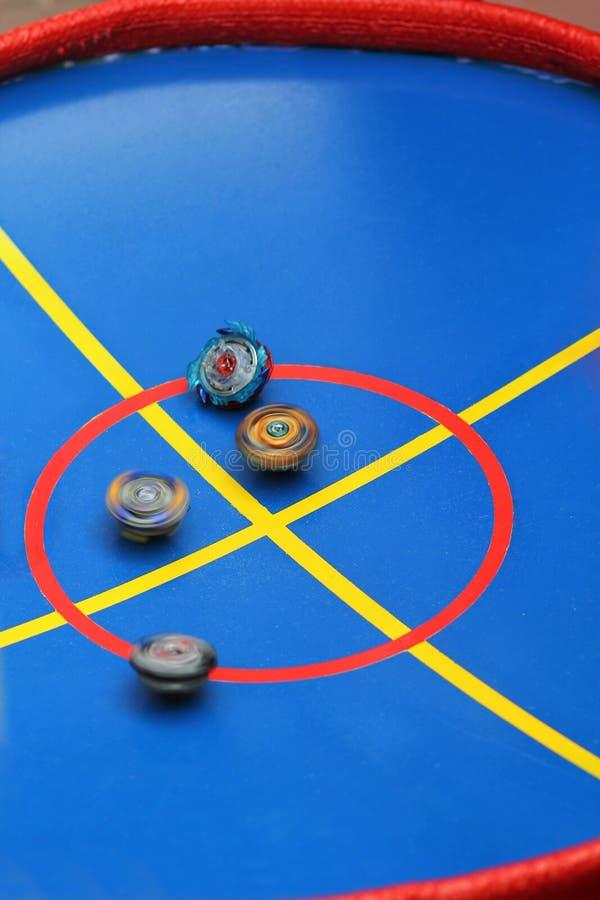 Trottole giranti sull'arena blu luminosa di battaglia immagini stock libere da diritti