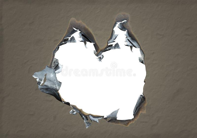 Trou brûlé en forme de coeur en papier. photographie stock