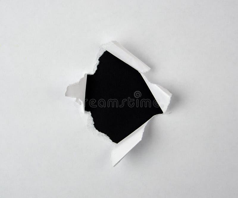 trou d?chir? rond avec les bords tordus en livre blanc photo libre de droits