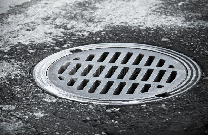 Trou d'homme d'égout sur la route goudronnée urbaine image libre de droits