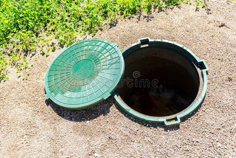 Trou d'homme sans garantie ouvert d'égout de fosse septique rurale avec p vert photos stock