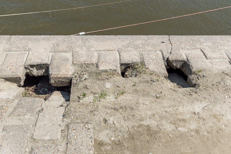 Trou dangereux pour des piétons sur le trottoir endommagé avec les briques cassées sur la rue urbaine de ville près de l'eau  image stock