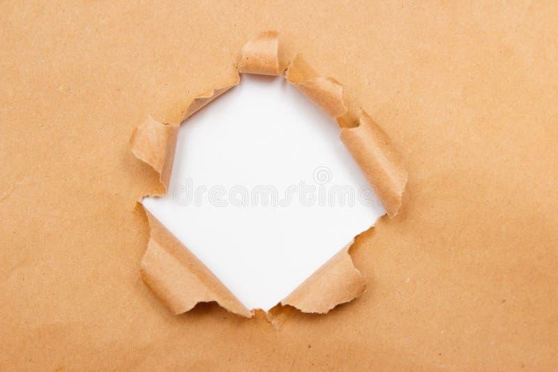 Trou dans la feuille brune de papier de métier avec les bords déchirés Centre blanc d'isolement, chemin de coupure inclus Vue sup images libres de droits