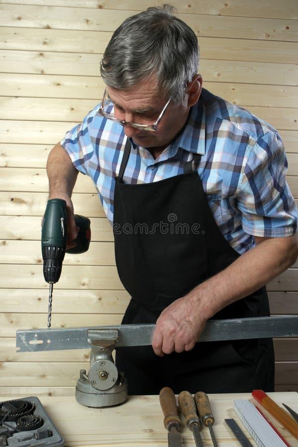 Trou de perçage supérieur de charpentier dans la planche en métal, dans son atelier images stock
