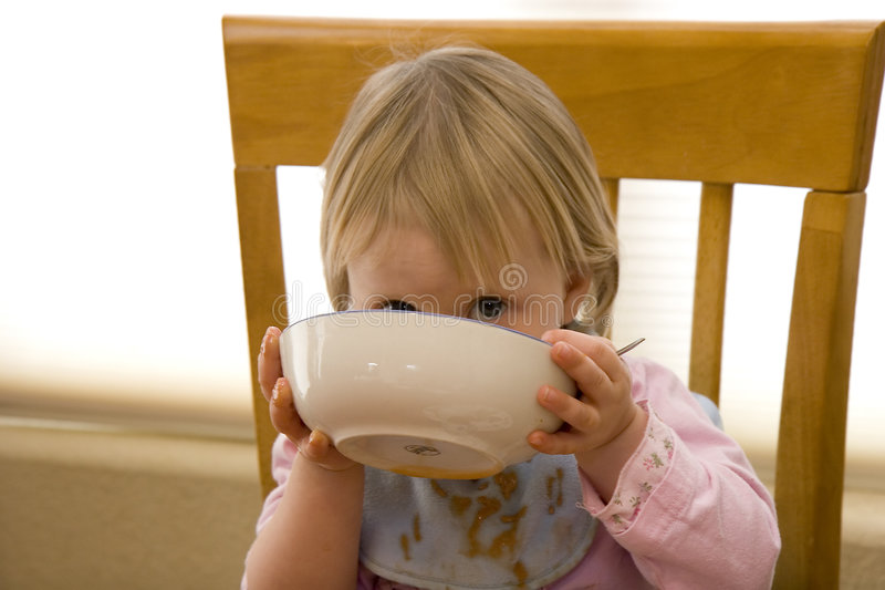 In trouble. Little toddler smiles over her messy mouth and bowl royalty free stock image