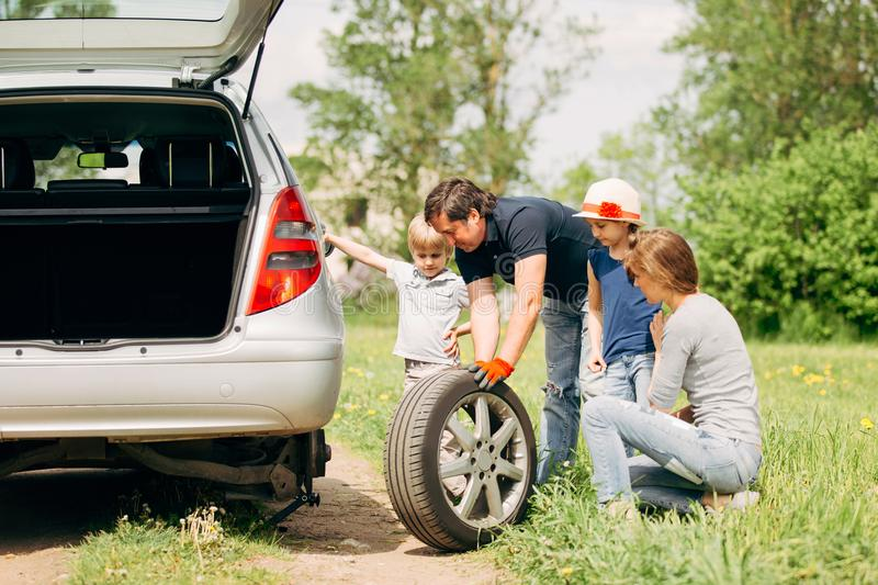Family friendly changes the tyre on the car stock image