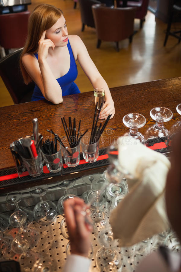 Troubled attractive woman having a flute of champagne royalty free stock photos