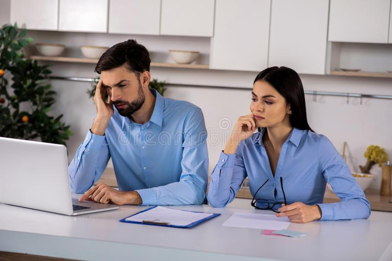 Troubled business colleagues sitting at the table stock images