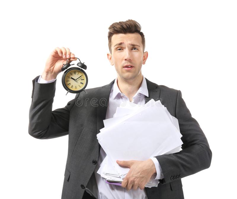 Troubled businessman with alarm clock on white background. Time management concept stock photo