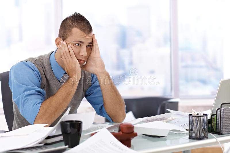 Troubled businessman at desk royalty free stock photography