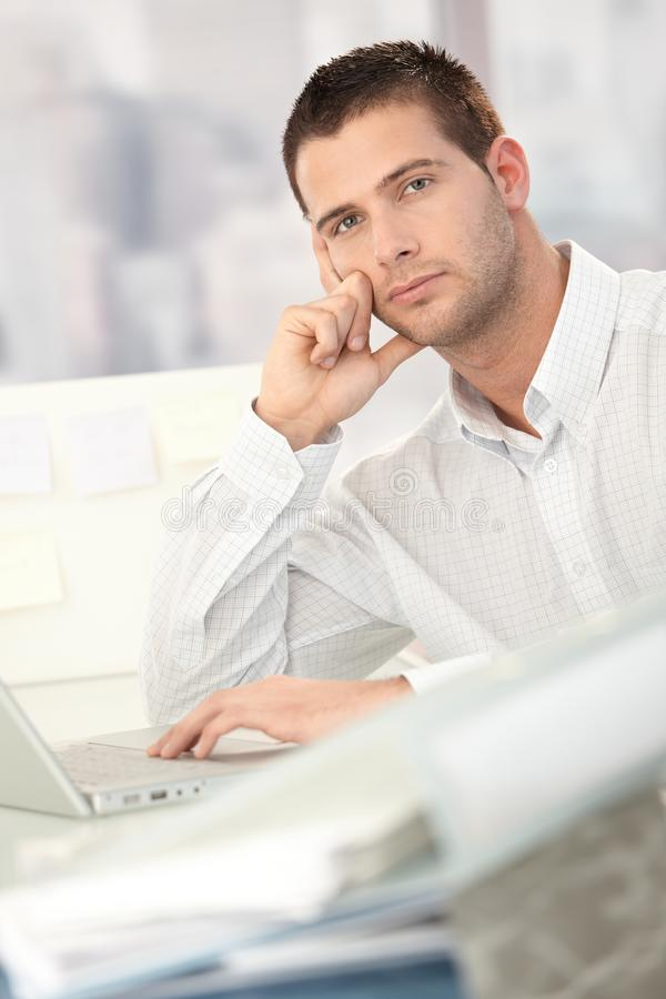 Troubled Businessman Sitting At Desk Stock Image