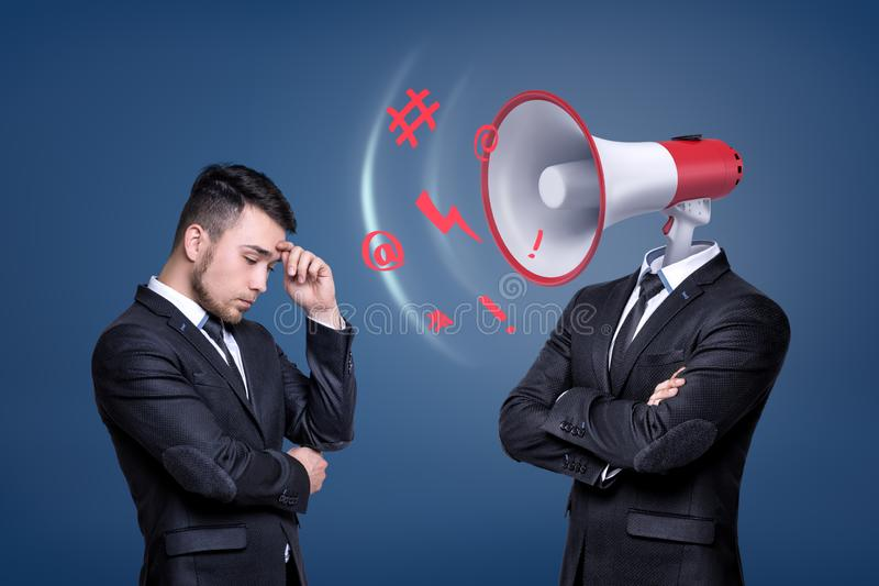 A troubled businessman stands near another man with a large shouting megaphone instead of his head. royalty free stock image