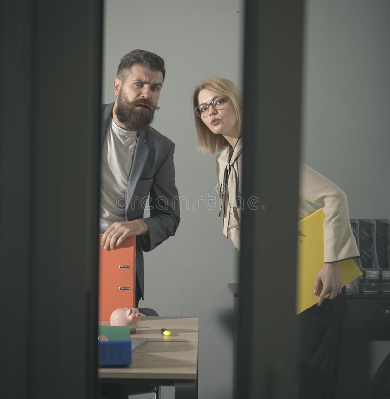 Troubled colleagues look out modern office with glass walls. Business couple at meeting. Bearded man and woman with royalty free stock images