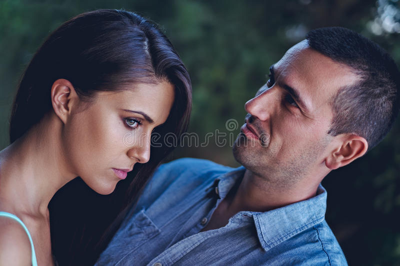 Troubled couple hugging in the park stock photos