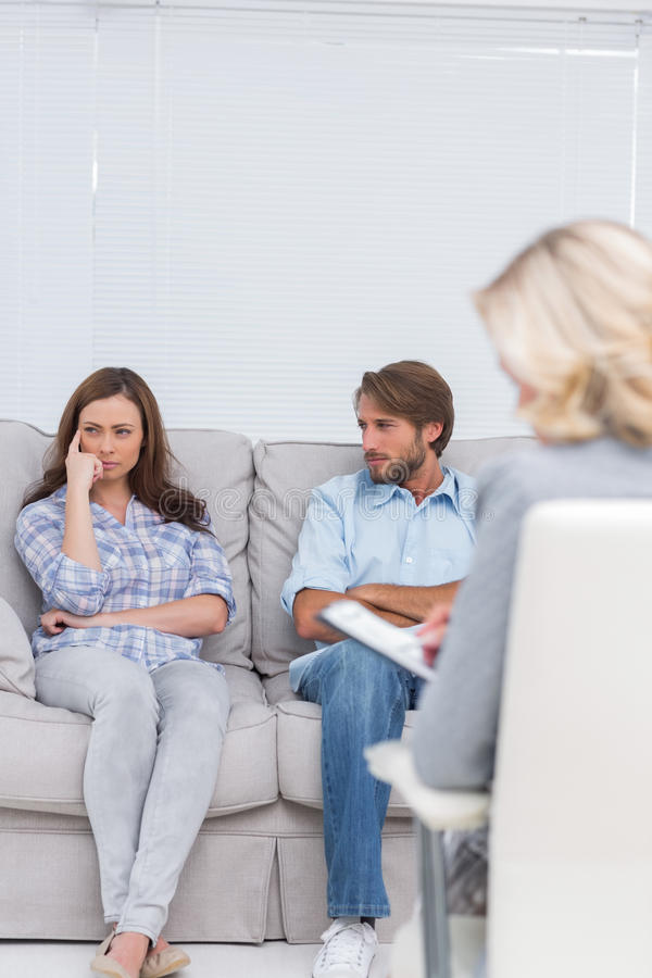 Troubled Couple Sit With Arms Folded Stock Image
