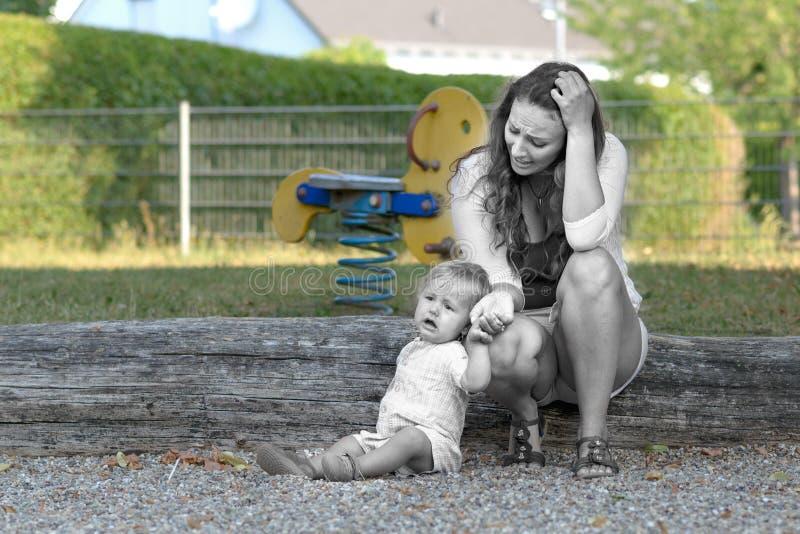 Troubled forçou a mãe nova com seu filho do bebê imagens de stock
