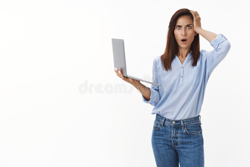 Troubled forgetful adult woman forgot important thing, touch head, stare camera ambushed distressed, hold laptop stock images